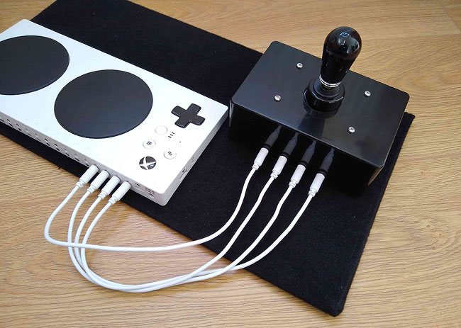 Rear of 4 Switches Joystick and Xbox adaptive Controller, with four short white patch cables linking the joystick to the XAC d-pad sockets.