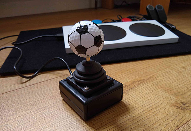 Golf Ball soccer ball / football style on top of a OneSwitch Zik-Zak joystick with Xbox Adaptive Controller in the background.