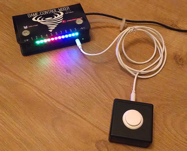 White push button in a small black box, attached by a thin coiled white patch lead to a Game Control Mixer, with rainbow coloured light bar on the front.