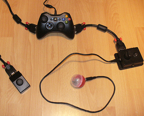 Image of a black adapted Xbox 360 joypad, connected via chunky Lindy SVGA cables to a box with a dial, on/off switch and two sockets. One socket for a switch, the other for a Vibro Capsule (Red and clear one with motor inside attached). On the other side an external thumbstick in a small sloping black case is attached.