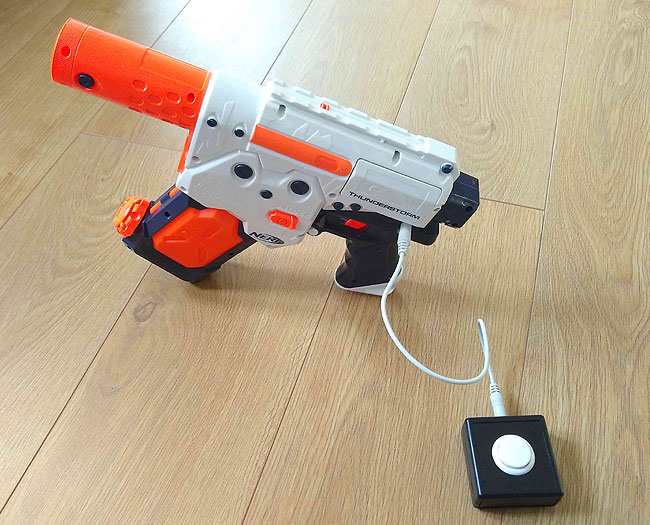 Switch adapted NERF Thunderstorm battery powered water pistol, standing up, with a small SANWA switch plugged in.