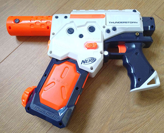 Orange, white and navy blue plastic water pistol with accessibility switch socket.