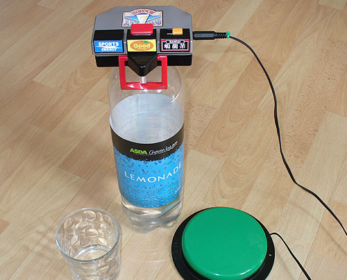 Switch Adapted drink dispenser, on top of a large Lemonade bottle by a glass and green accessibility switch.