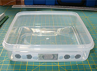 Tupperware box with drilling template blue-tacked into place.