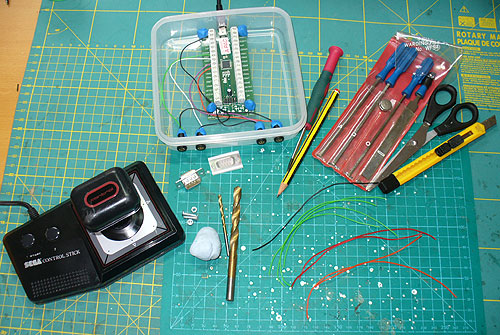 The basic parts needed from top left clockwise: 5g pouch of SUGRU rubber compound, switch sockets and wire, Ultimarc A-PAC PCB, Tupperware sandwich box, USB lead.