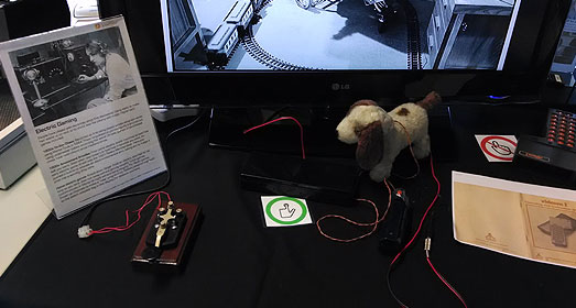 Telegraph key controlled slide-show on the history of game accessibility. Switch adapted 1970s battery powered toy dog. Green touch sign.