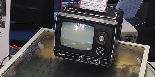 Black and white TV on top of perspex box housing Meadows' 1975 game Drop Zone IV. TV screen shows a very old black and white arcade video game screen.