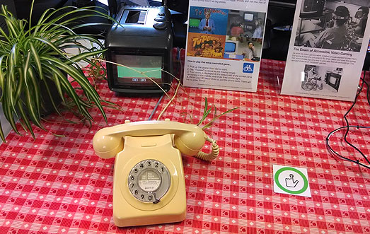 Yellow GPO Telephone on a red and white chequered table cloth, next to a small colour portable TV and Spider plant. Part of a TV Powww! display.