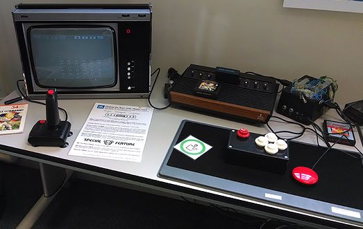 Atari VCS games machine next to an Ultra Black and White portable TV. One handed Quickshot joystick, Barrie Ellis switch interface from 1995 and Ken Yankelevitz Finger Tip controller from around 1981.