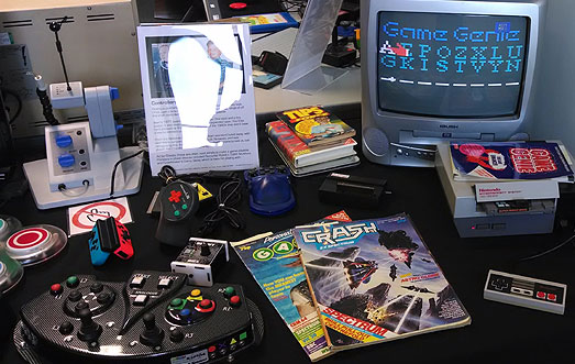 Various accessible game controllers, including a 3D printed Nintendo Switch hand-set, MERU custom arcade stick, Nintendo Hands Free Controller, DragonPlus RPG controller, cheat systems, Crash and PCG magazines and Nintendo NES running a Game Genie cheat cartridge.