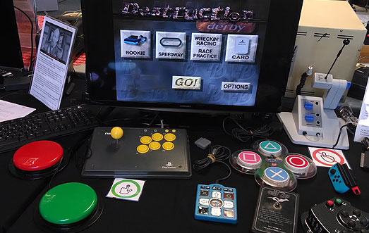 Switch adapted Namco Arcade Stick from 2001 by Barrie Ellis connected to Destruction Derby on a Playstation One. Also a Mini Dance Dance Revolution controller and Electro Kennel Club controller.