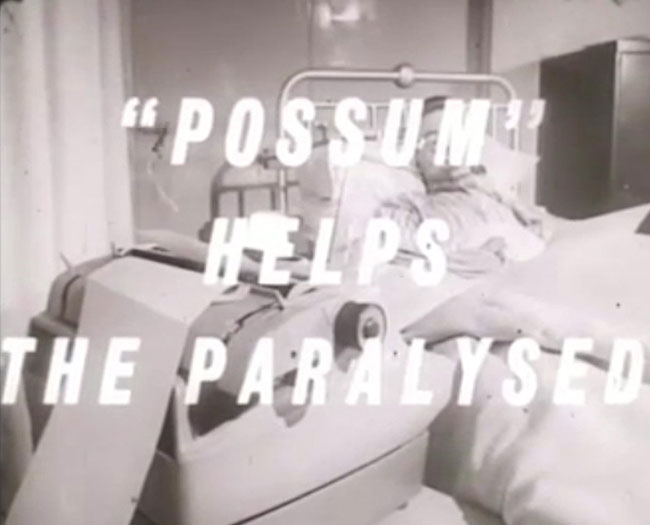 Possum Helps The Paralysed.  Black and white still from a short 1960s film from Possum. The image is of a man in pyjamas lying in bed, looking towards an electric typewriter.   White italic text overlays this scene, reading, Possum Helps the Paralysed.