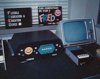 FRED 1972 stretched hexagonal computer in black. Simple control panel on front of switches and lights. Smiley face and coloured dots speckle the front panel. RCA printed on bottom. Black and White CRT RCA TV to right. Tape deck and cards. In back-ground two boards on window-shelf. Flexible Recreation and Education Device. And Can Computers be fun? Fred is for all ages. With pink smiley.