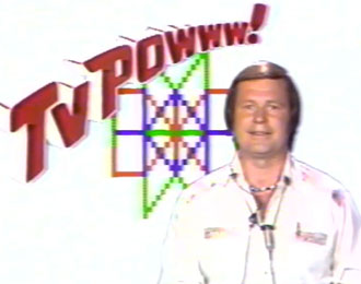 TV Powww! With TV presenter in late 70s US white jumpsuit with Quadradoodle graphics in the background.
