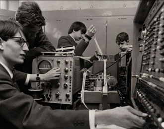 Black and white photos of 1960s school children programming a huge 1950s computer.
