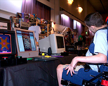 Game Accessibility Museum - Chris Myers playing a one-switch video game at a show.